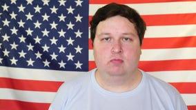 Hombre confiado en 30s temprano que cabecea su cabeza sí en el fondo de una bandera de los E.E.U.U. almacen de video
