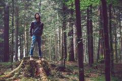 Hombre confiado que se coloca en el bosque Foto de archivo libre de regalías