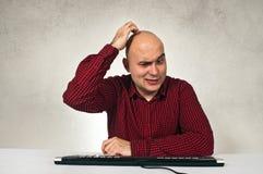 Hombre confuso en la tabla de la oficina fotos de archivo libres de regalías