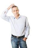 Hombre confuso que rasguña su cabeza Imágenes de archivo libres de regalías