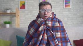 Hombre congelado cubierto en la helada envuelta en una manta con los guantes en la sala de estar y las miradas en la cámara almacen de metraje de vídeo