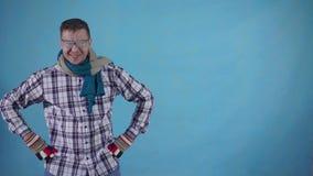 Hombre congelado enérgico positivo cubierto con helada en guantes y bufanda en espacio azul de la copia del fondo almacen de video