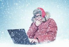Hombre congelado en el funcionamiento rojo de la ropa y de vidrios del invierno en un ordenador portátil en la nieve Frío, helada imagenes de archivo