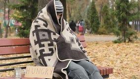 Hombre congelado sin hogar hambriento que se sienta en banco y que intenta conseguir caliente, pobreza almacen de video