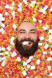 Hombre contento en dulces que muerde la melcocha Foto de archivo libre de regalías