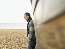 Hombre contra el casco de madera del barco en la playa Foto de archivo