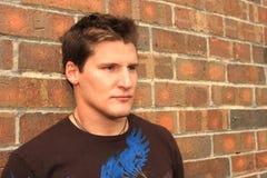 Hombre contra la pared de ladrillo Foto de archivo
