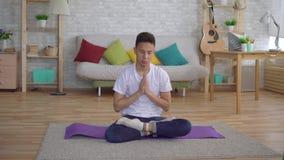 Hombre coreano joven que hace la yoga que se sienta en la estera metrajes