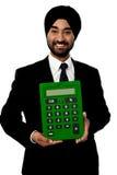 Hombre corporativo que muestra la calculadora verde grande imagenes de archivo