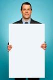 Hombre corporativo que sostiene la cartelera en blanco blanca grande Imagen de archivo libre de regalías