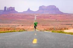 Hombre corriente - corredor en el camino por el valle del monumento Fotos de archivo libres de regalías
