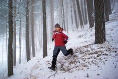 Hombre corriente en bosque de la montaña del invierno Foto de archivo libre de regalías