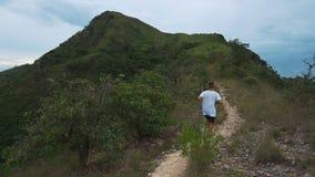 Hombre corriente en el camino de la montaña Muchacho de la aptitud del deporte que ejercita afuera en montaña Goce sano vivo de l metrajes