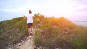 Hombre corriente en el camino de la montaña Muchacho de la aptitud del deporte que ejercita afuera en montañas Goce sano vivo de  Foto de archivo libre de regalías