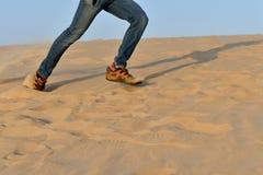 Hombre corriente en la arena en el desierto como tiro del fondo Imagen de archivo libre de regalías