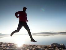 Hombre corriente Muchacho que corre rápidamente en la playa de la mañana Corredor del deportista, individuo que activa Foto de archivo