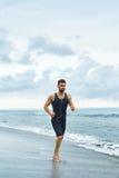 Hombre corriente que activa en la playa durante el entrenamiento de la aptitud al aire libre Deporte Foto de archivo