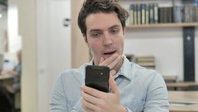 Hombre creativo chocado en temor mientras que usando Smartphone almacen de video