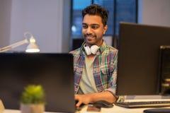 Hombre creativo con el ordenador portátil que trabaja en la oficina de la noche Imagenes de archivo