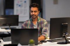 Hombre creativo con el ordenador portátil que trabaja en la oficina de la noche Foto de archivo libre de regalías
