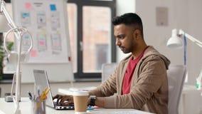 Hombre creativo indio que trabaja en el ordenador portátil en la oficina almacen de metraje de vídeo