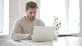 Hombre creativo que mecanografía en el ordenador portátil en oficina del desván almacen de metraje de vídeo