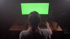 Hombre creativo que trabaja delante del ordenador Antes de él es una pantalla verde 4K MES lento almacen de metraje de vídeo
