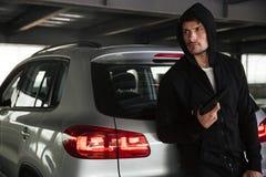 Hombre criminal con el arma que coloca el coche cercano en el estacionamiento Foto de archivo