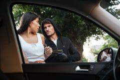 Hombre criminal peligroso con el arma que roba el coche de la mujer asustada imagenes de archivo