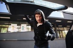 Hombre criminal que amenaza con el arma y el tronco de coche cerrado al aire libre Foto de archivo libre de regalías