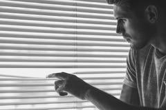 Hombre curioso observando a través de persianas horizontales fotos de archivo libres de regalías