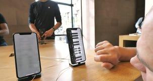 Hombre curioso que usa el app musical en nuevo smartphone del iPhone XS almacen de metraje de vídeo