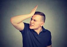 Hombre, dando una palmada a la mano en la cabeza que tiene duh un momento imagen de archivo