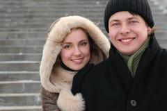 Hombre de abarcamiento de la muchacha de posterior y de la sonrisa Foto de archivo libre de regalías