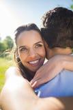 Hombre de abarcamiento de la mujer cariñosa y feliz en el parque Imagen de archivo libre de regalías