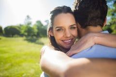 Hombre de abarcamiento de la mujer cariñosa y feliz en el parque Imagen de archivo