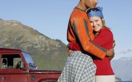 Hombre de abarcamiento de la mujer contra Jeep And Mountains Imagen de archivo