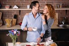 Hombre de abarcamiento de la mujer en la cocina Foto de archivo libre de regalías