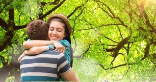Hombre de abarcamiento de la mujer feliz contra árboles Fotos de archivo libres de regalías