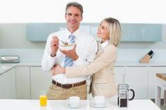 Hombre de abarcamiento de la mujer feliz en la cocina Foto de archivo libre de regalías