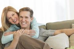 Hombre de abarcamiento de la mujer feliz en Sofa At Home Fotos de archivo libres de regalías