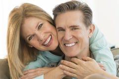 Hombre de abarcamiento de la mujer feliz en Sofa At Home Imagenes de archivo