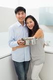 Hombre de abarcamiento de la mujer joven en cocina Imagen de archivo