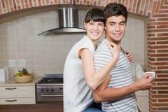 Hombre de abarcamiento de la mujer joven en cocina Imagenes de archivo