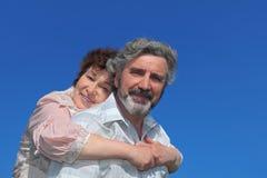 Hombre de abarcamiento de la mujer mayor de posterior y de la sonrisa Foto de archivo libre de regalías