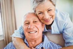 Hombre de abarcamiento de la mujer mayor en casa Imágenes de archivo libres de regalías