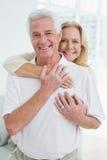 Hombre de abarcamiento de la mujer mayor feliz de detrás Imagen de archivo libre de regalías