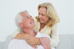 Hombre de abarcamiento de la mujer mayor feliz de detrás Fotos de archivo libres de regalías