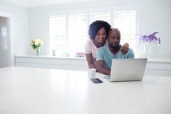 Hombre de abarcamiento de la mujer mientras que usa el ordenador portátil Imagenes de archivo