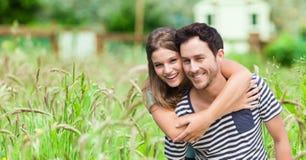 Hombre de abarcamiento feliz de la mujer joven en campo Imagen de archivo libre de regalías